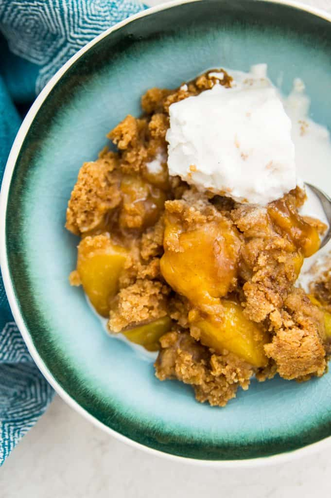 A bowl of peach cobbler with a scoop of vanilla ice cream on top