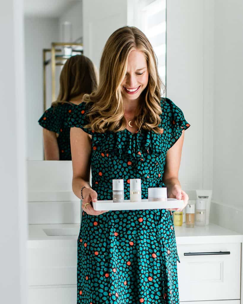 A girl in a floral dress holding Beautycounter products on a tray