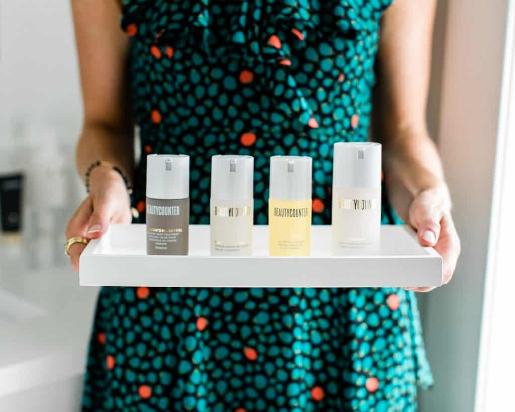 A girl holding a tray of Beautycounter skincare products that are used for acne