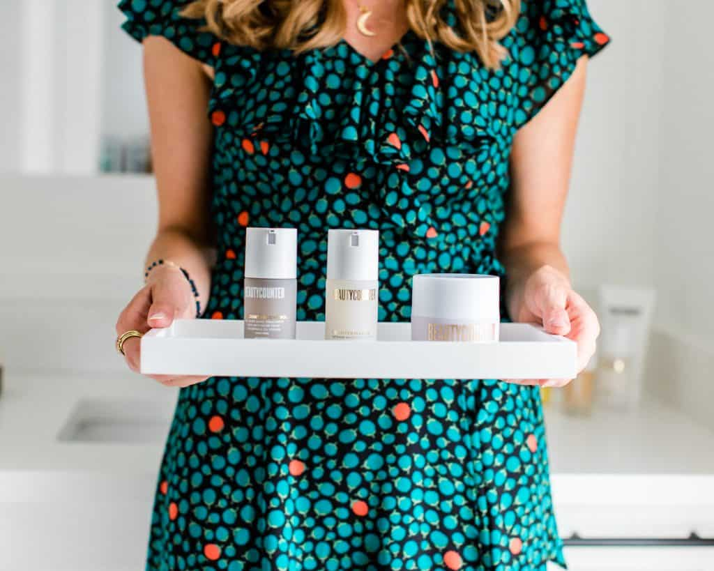 A girl holding a tray filled with three Beautycounter products