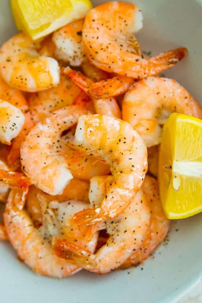 A bowl full of air fryer frozen shrimp with slices of lemon