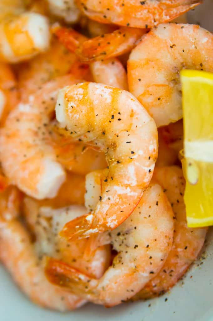 A close up photo of air fryer frozen shrimp in a bowl with lemon slices