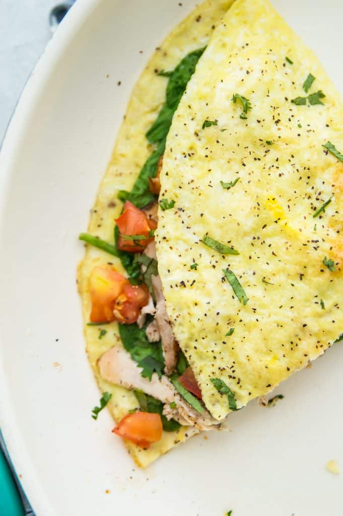 A chicken omelette that has been cut in half and filled with tomato and spinach