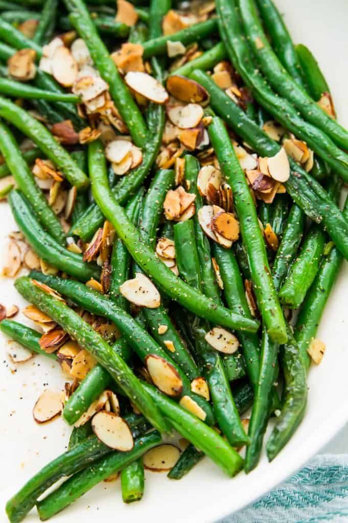 A dish filled with keto green beans topped with slivered almonds