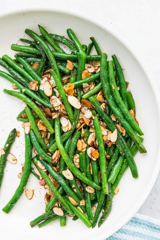 A pan full of keto green beans topped with slivered almonds