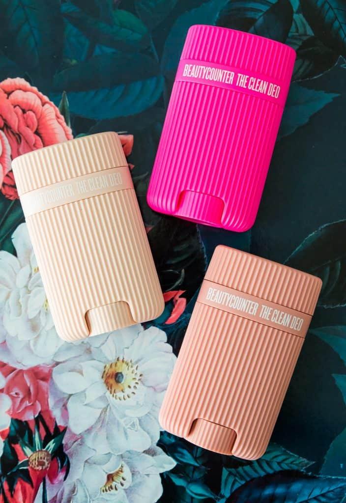 three Beautycounter deodorants on a floral mat