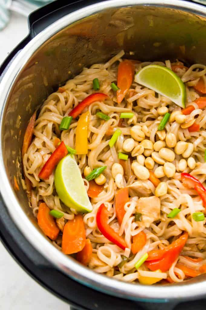 A large batch of Instant Pot Pad Thai with lime wedges and peanuts inside an Instant Pot