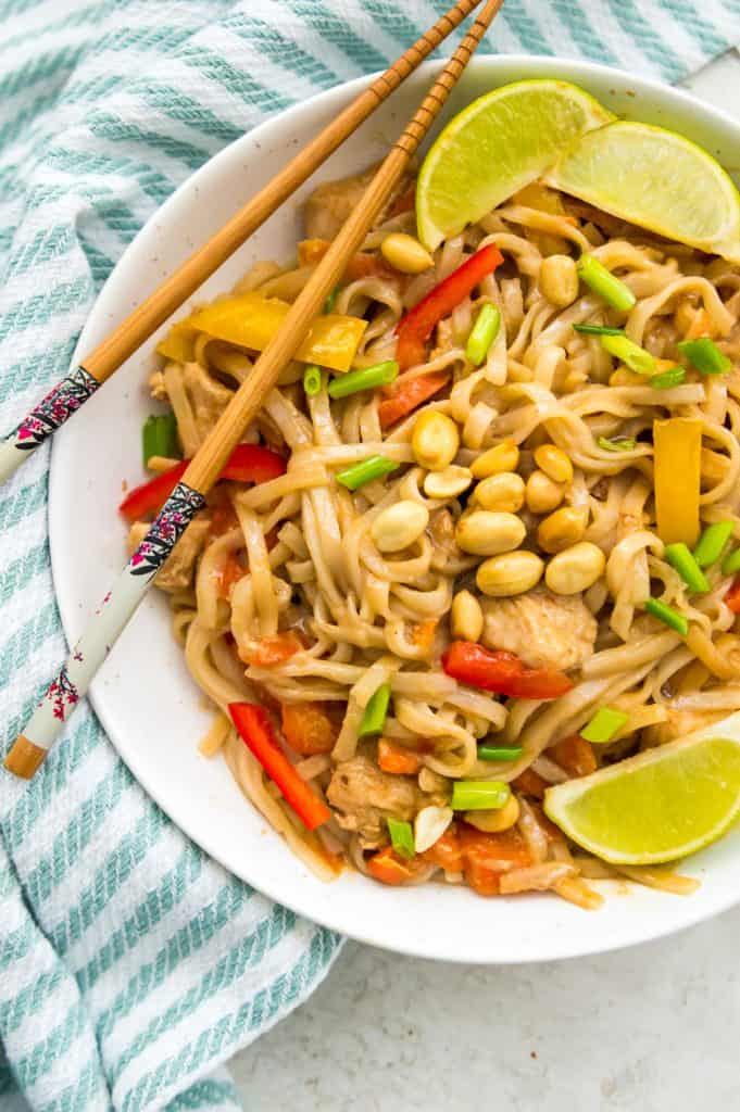 A bowl of Instant Pot Pad Thai garnished with lime wedges and peanuts