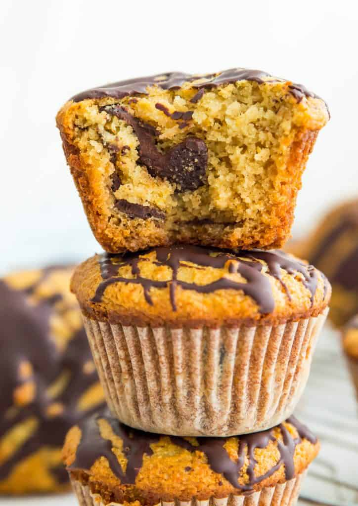 Paleo orange chocolate chunk muffins stacked in a pile with a bite out of the top one