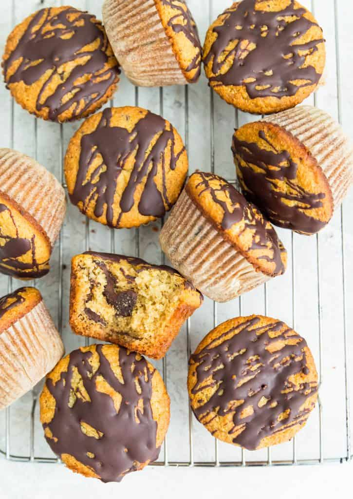 paleo orange chocolate chunk muffins on a rack with a bite out of one of the muffins