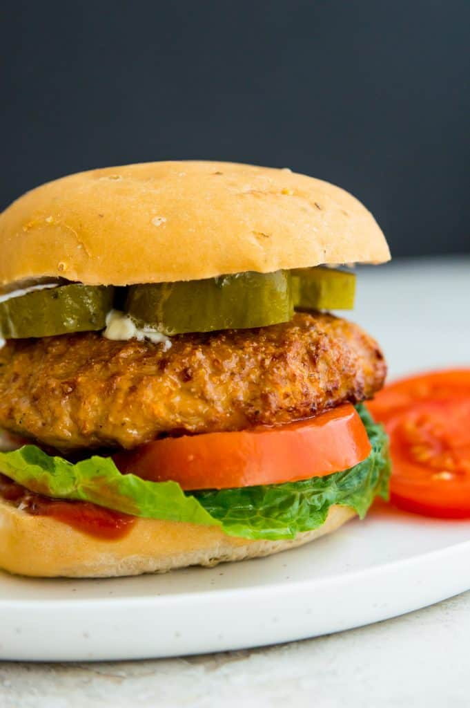 A turkey burger cooked in an air fryer on a plate with pickles, tomatoes and potato chips