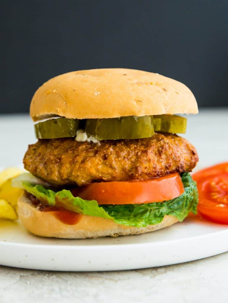 An air fryer turkey burger on a bun on a plate with tomatoes and chips