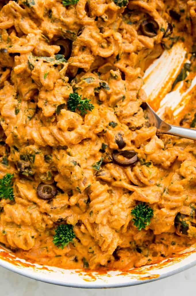 A close up shot of vegan sun dried tomato pasta in a pan with a spoon
