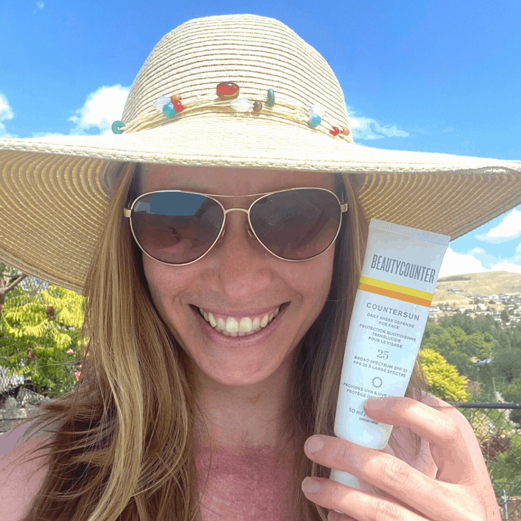 A girl in a hat and sunglasses holding a tube of Beautycounter sunscreen near her face
