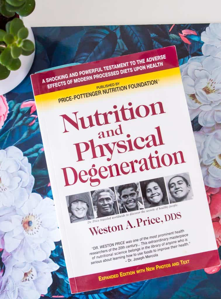 Nutrition and Physical Degeneration book on a white desk with a plant