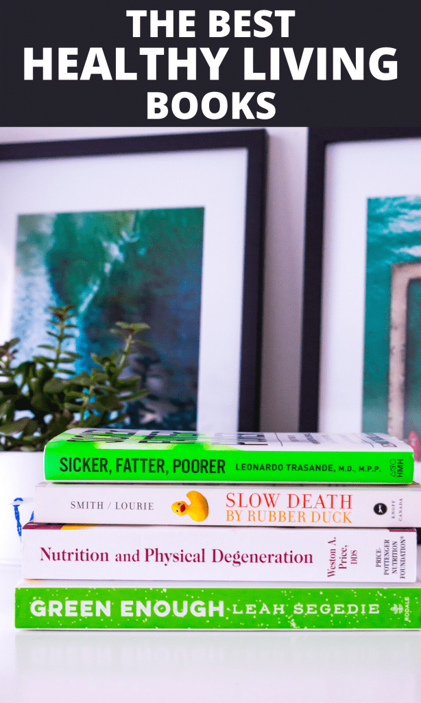 A stack of wellness books on a desk with a plant