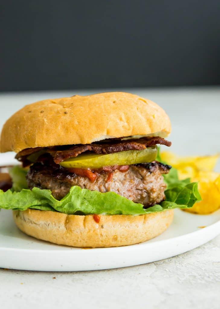 A duck burger on a plate in a bun with chips