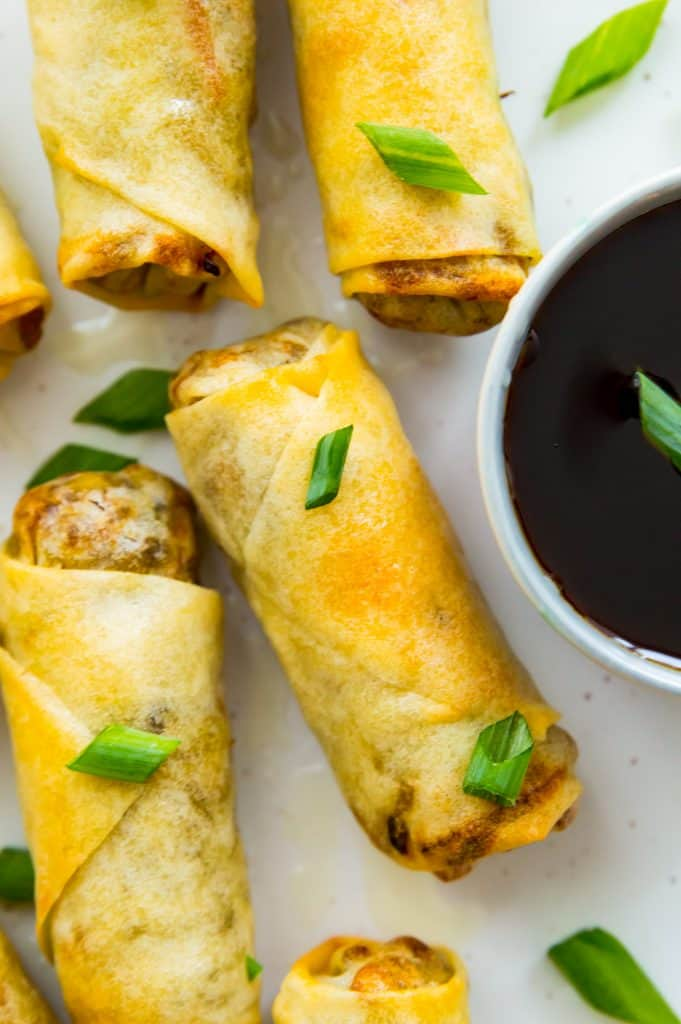 Egg rolls on a plate with a dish of soy sauce and garnished with green onion
