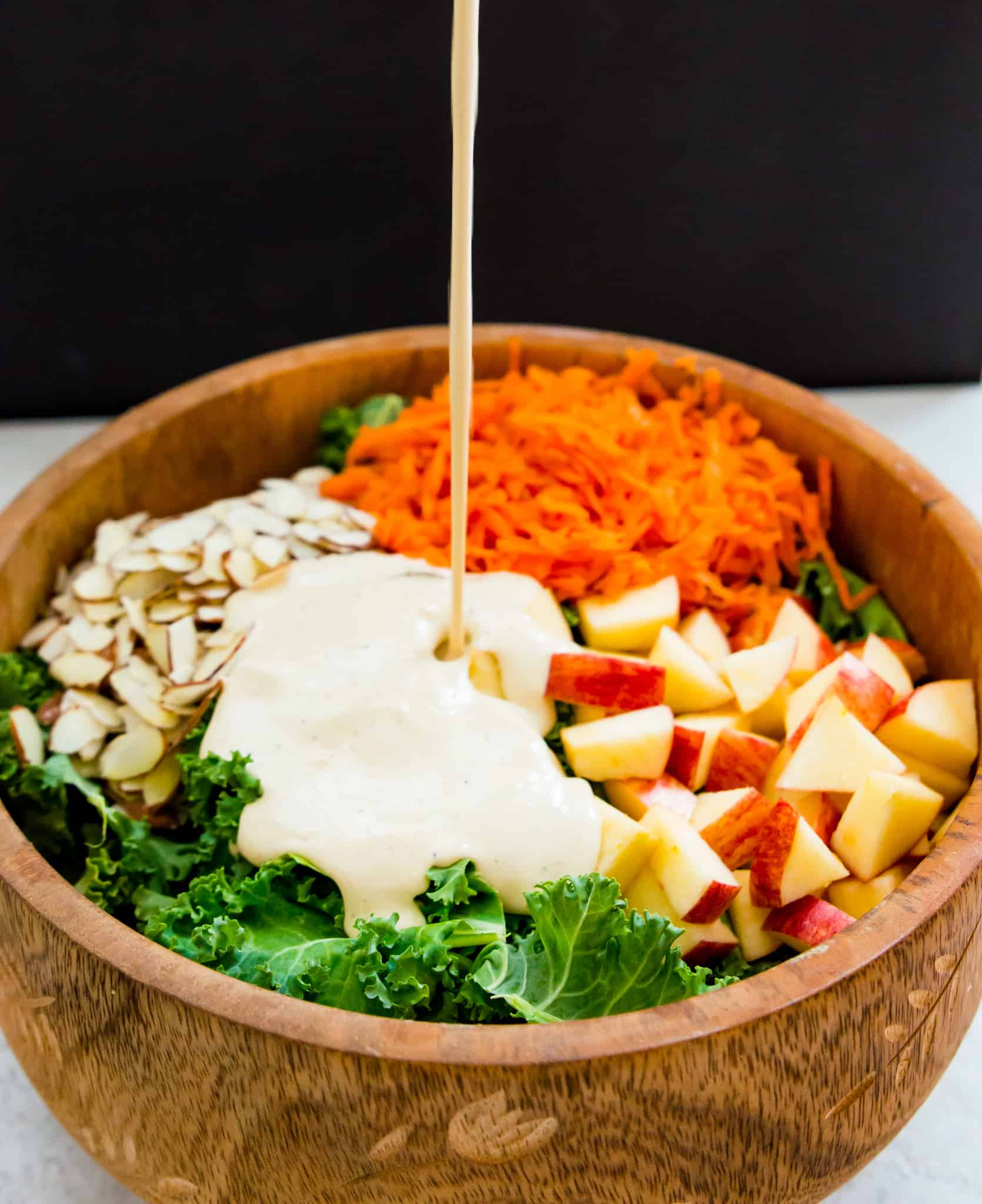 A creamy dressing poured over a wooden mixing bowl of kale, almonds, carrots, and apples | Kale Slaw with Apples