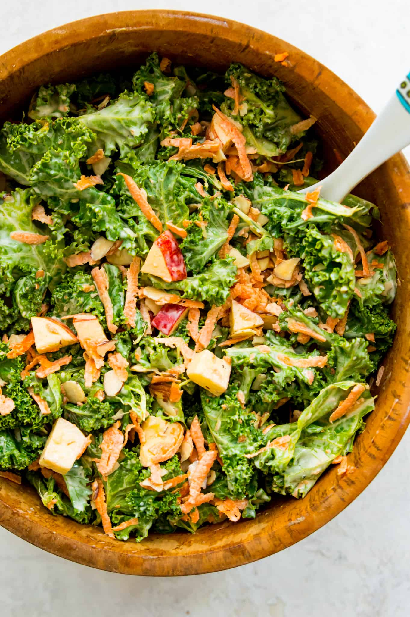Bites of red apple, carrots, slivered almonds, and fresh kale in a wooden mixing bowl with dressing | Kale Slaw with Apples