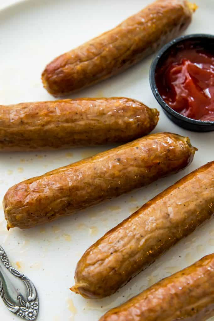 A plate with cooked bratwurst sausages with a side of ketchup