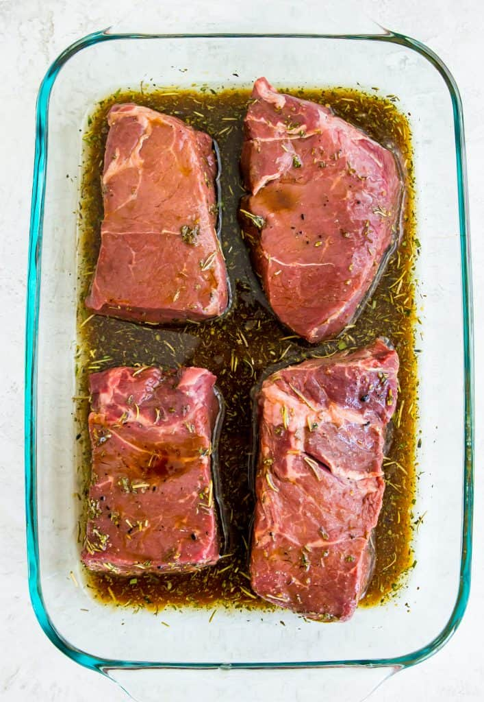 Four steaks in a glass dish with low carb steak marinade