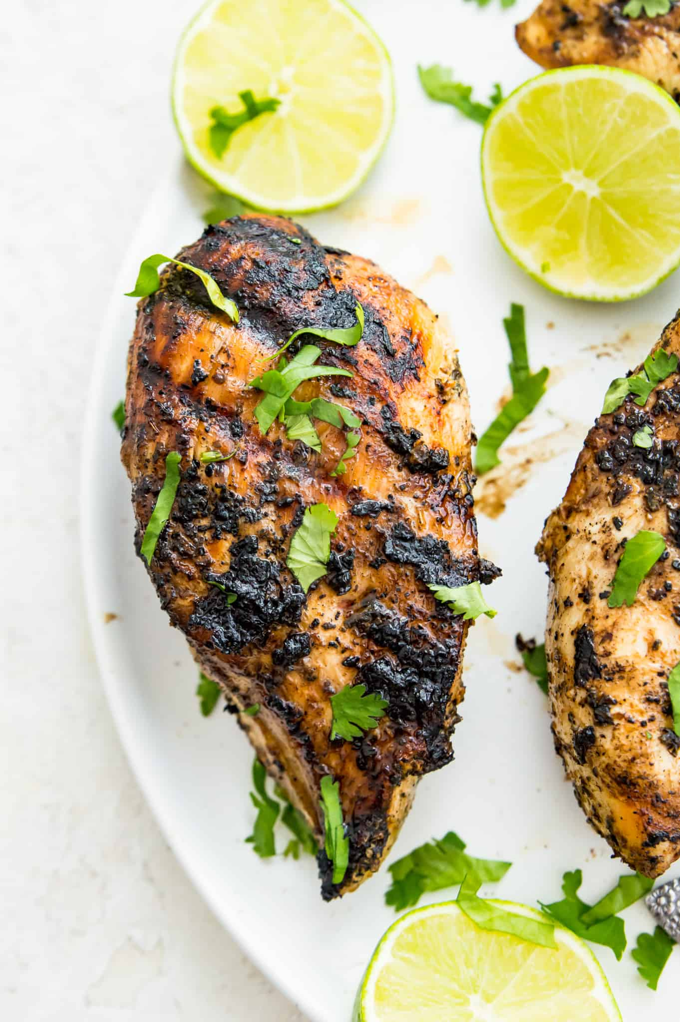 Overhead shot of charred grilled Mexican chicken garnished with cilantro and surrounded by limes