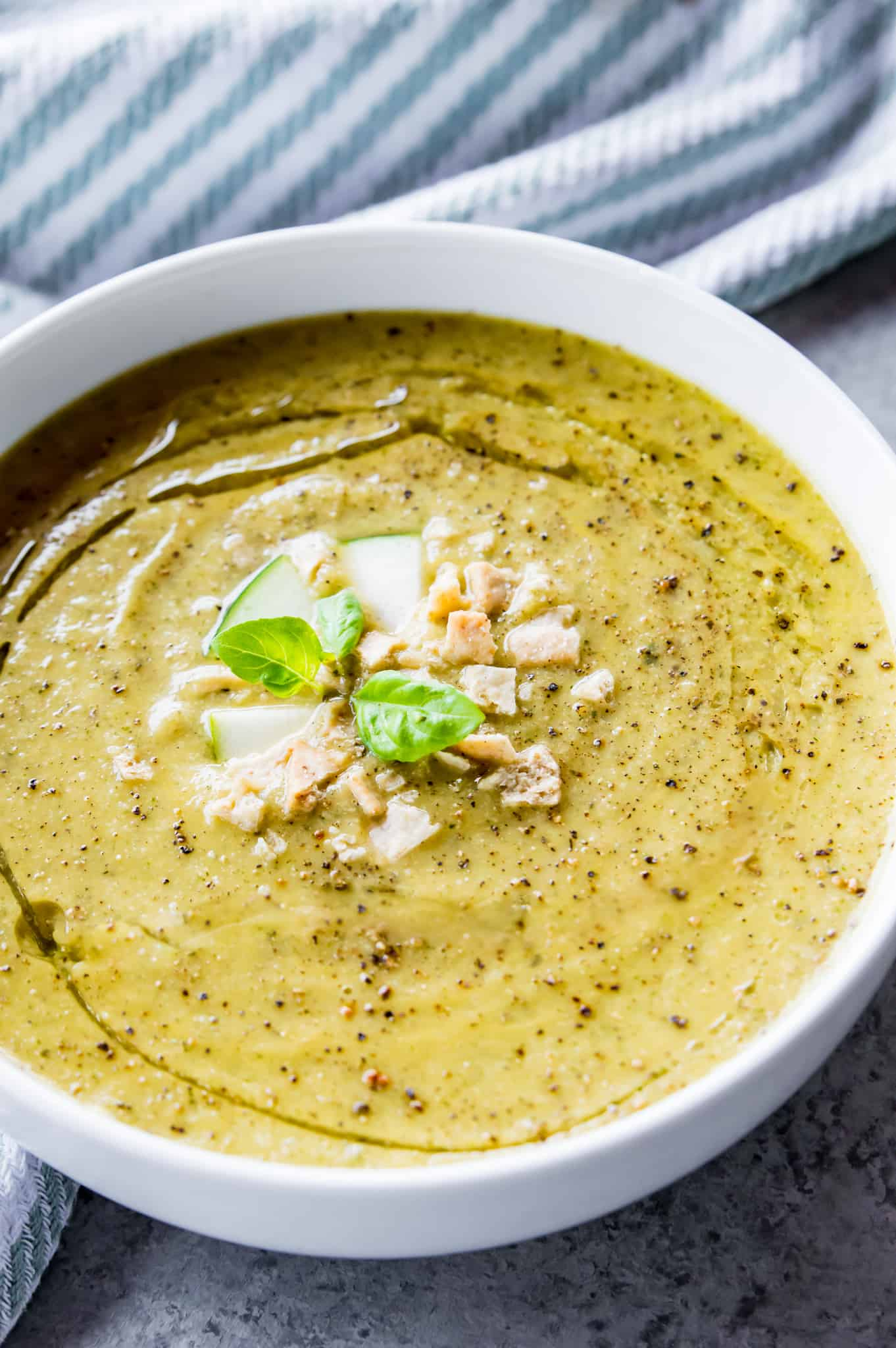 Vegan Zucchini Soup Recipe | A bowl of vegan zucchini soup topped with crushed crackers and fresh basil