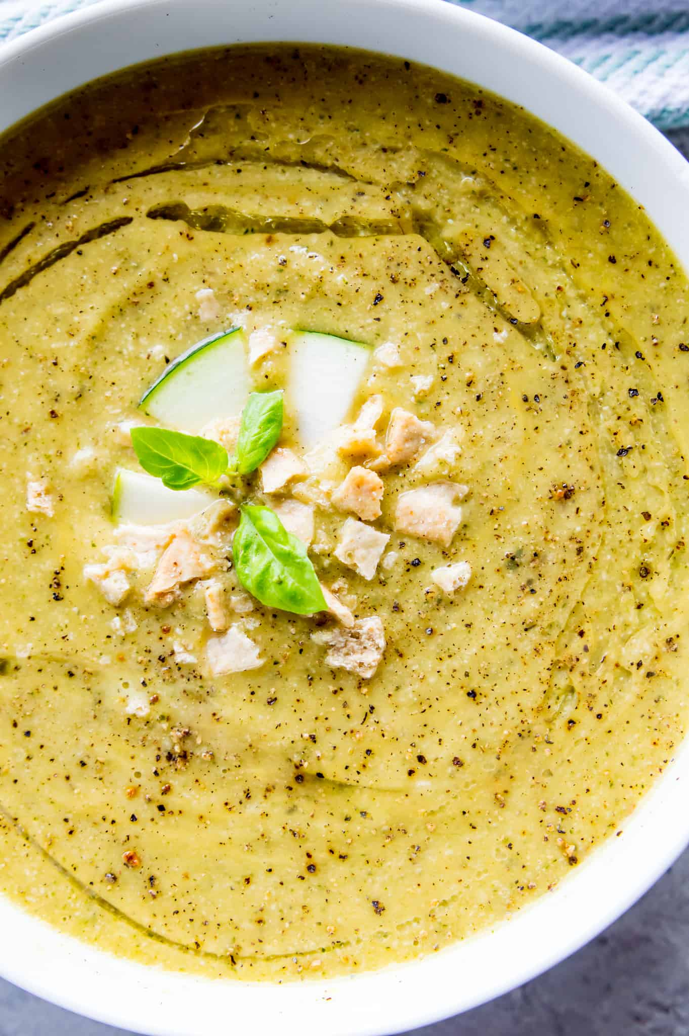 A bowl of creamy vegan zucchini soup topped with crackers and basil