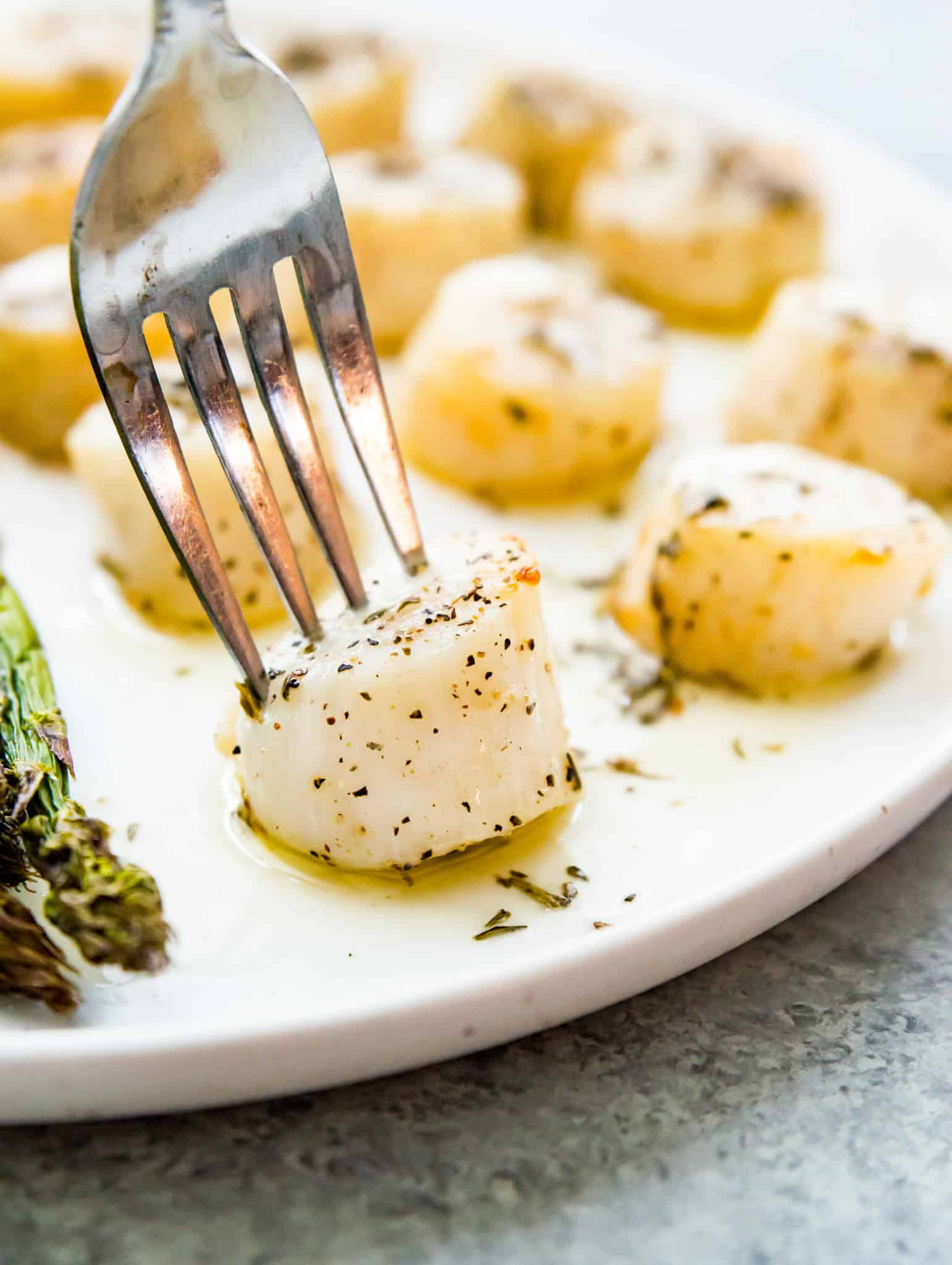 A plate of cooked scallops with a fork in one of the scallops