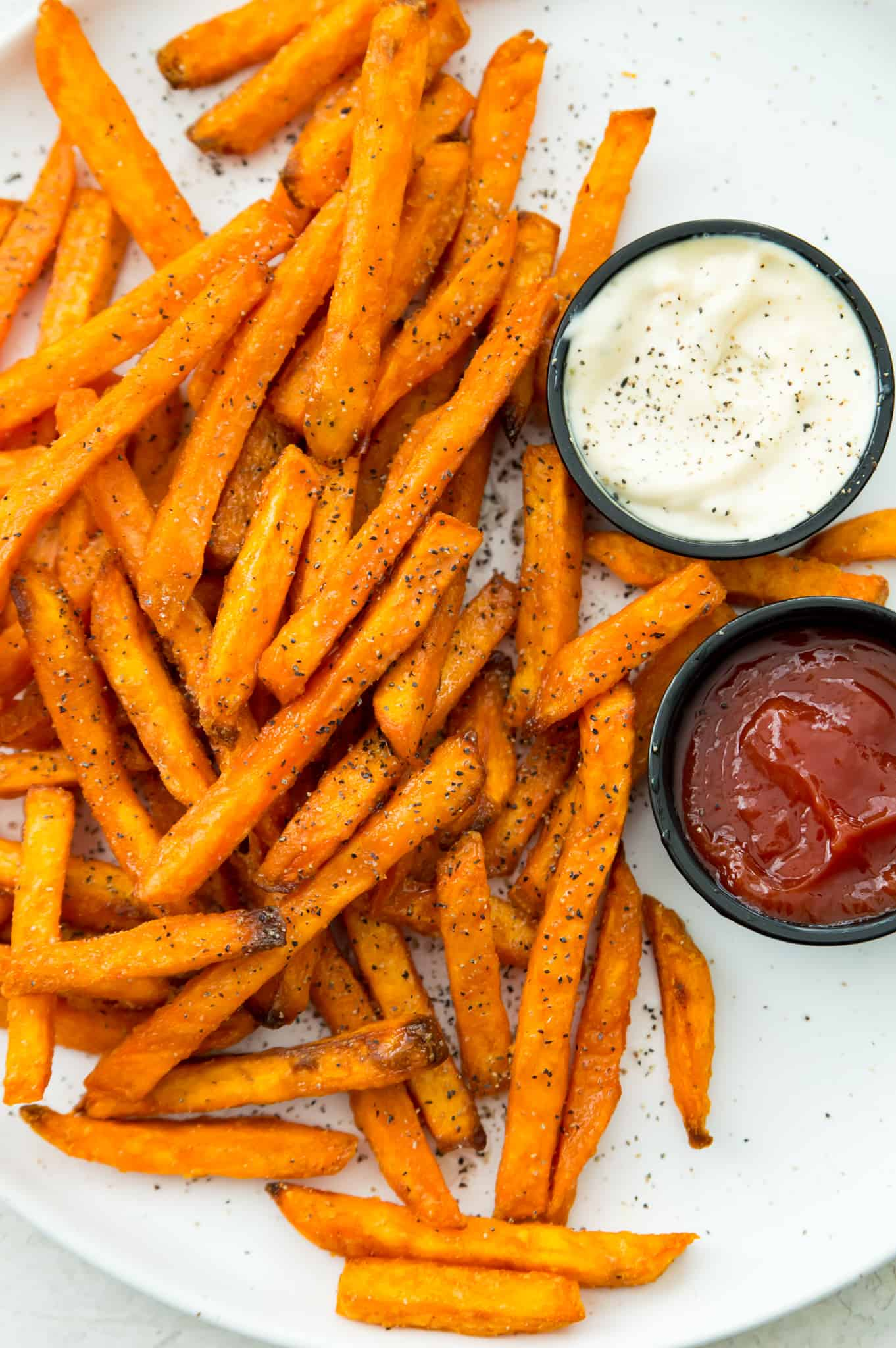 A plate of cooked sweet potato fries with ketchup and aioli on the side