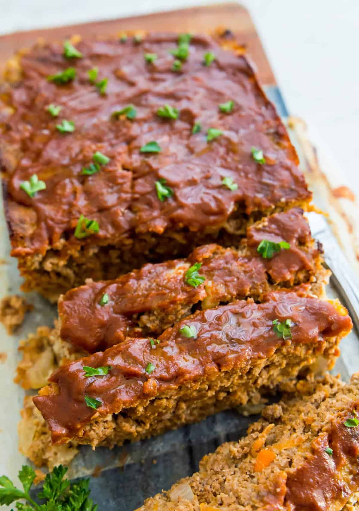 Whole30 meatloaf topped with bbq sauce and sliced into pieces